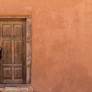 Rustic Wooden Door on Adobe Building Wall